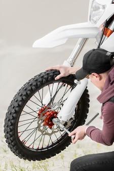 バイクを修理しようとしているクローズアップの成人男性