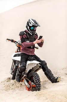 Мотоциклист с шлемом просматривает мобильный телефон
