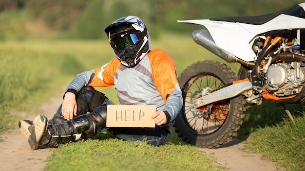 Портрет всадника мотоцикла, держащего знак помощи