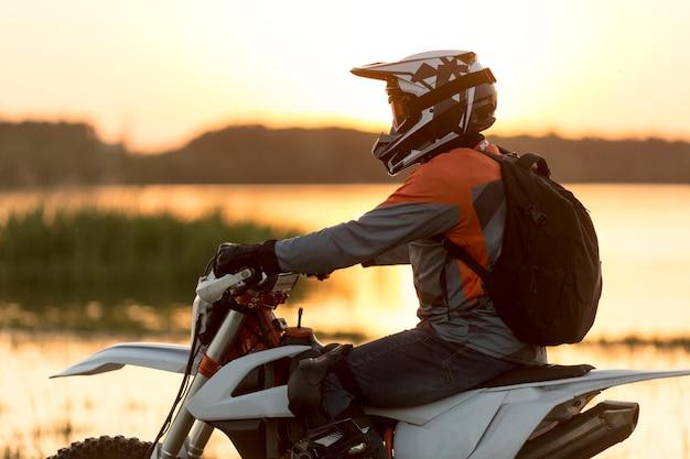 バイクに乗って楽しむスタイリッシュな男の側面図