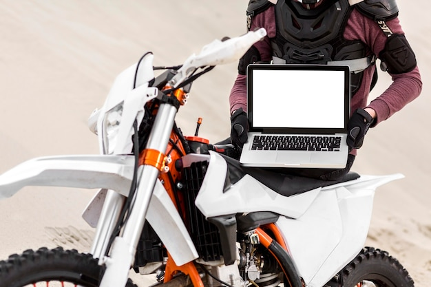 ラップトップを保持しているスタイリッシュなバイクライダー