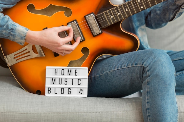 Крупным планом женщина играет на гитаре у себя дома