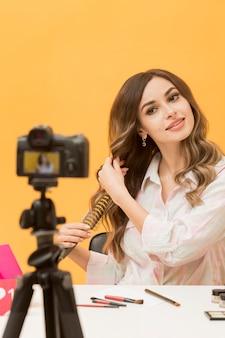 カメラの髪をブラッシングの女性の肖像画