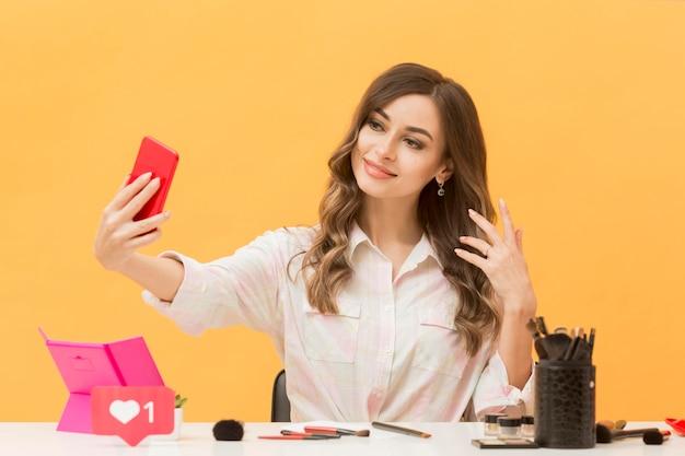 美しい女性が携帯電話で自分を記録