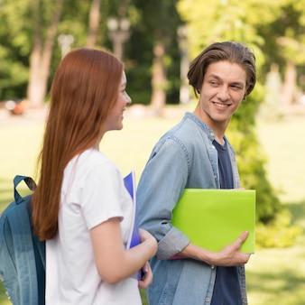 Подростки вместе гуляют в кампусе