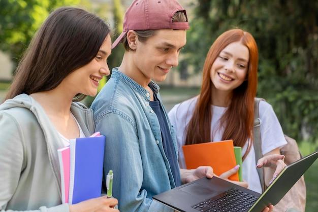 Группа подростков обсуждает проект в кампусе