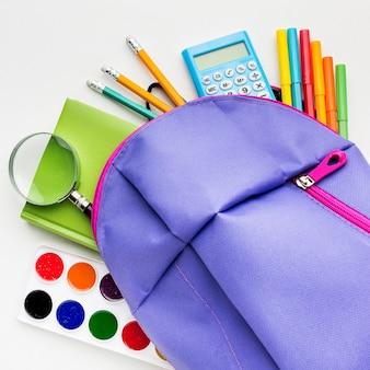 水彩とバックパックを備えた学校の必需品のフラットレイアウト