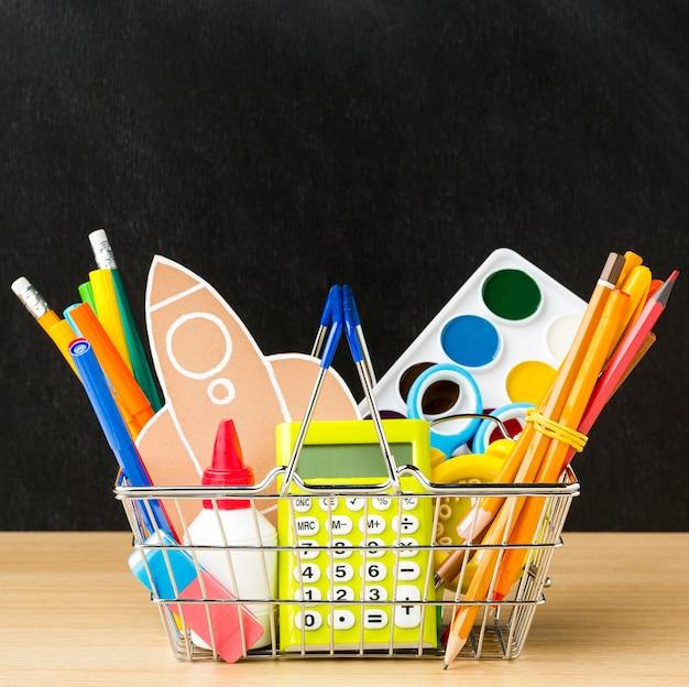 Вид спереди корзины с обратно в школу предметов первой необходимости