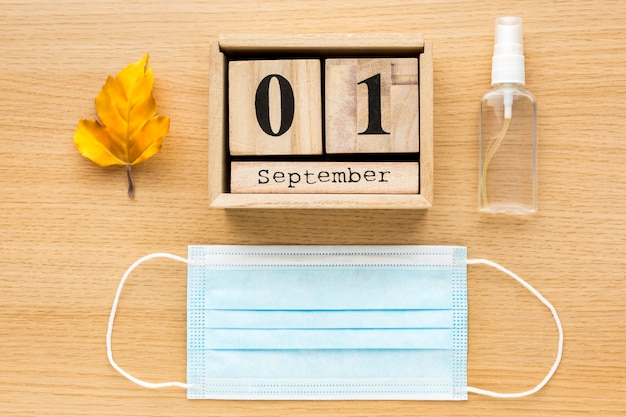 Вид сверху обратно в школу предметов первой необходимости с медицинской маской и календарем