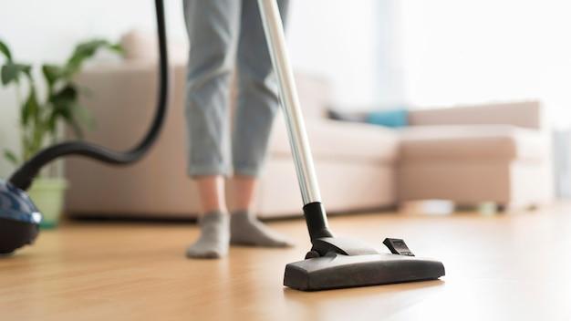 Вид спереди женщины с помощью пылесоса в комнате