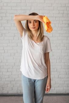 Вид спереди усталой женщины, держащей чистящую ткань