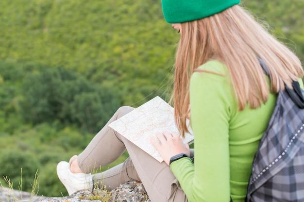 屋外の地図をチェックするクローズアップの若い旅行者