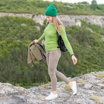 野外を歩いているスタイリッシュな若い旅行者