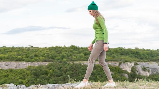 サイドビューの若い女性が屋外での散歩を楽しんで