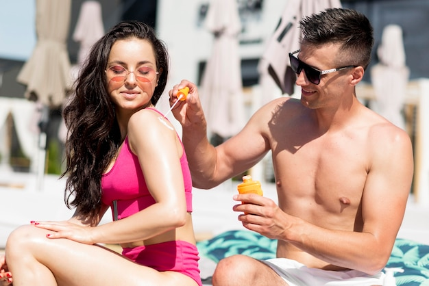 日焼け止めとビーチでかわいいカップル