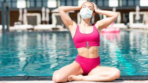 Женщина в маске у бассейна
