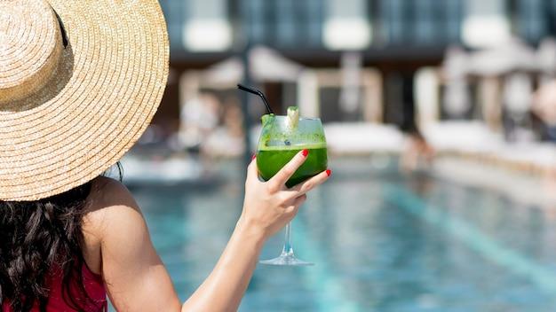 ドリンクを飲みながらプールでリラックスできる女性