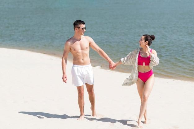 Длинный выстрел счастливая пара на пляже