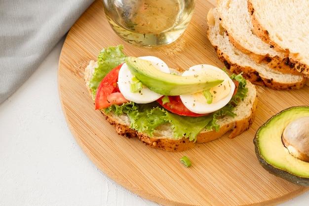 木の板にゆで卵とトマトのサンドイッチ