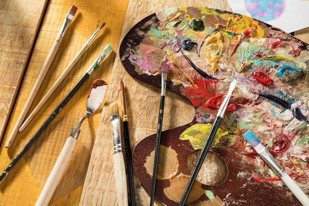 Палитра красок с кистями и шпателем