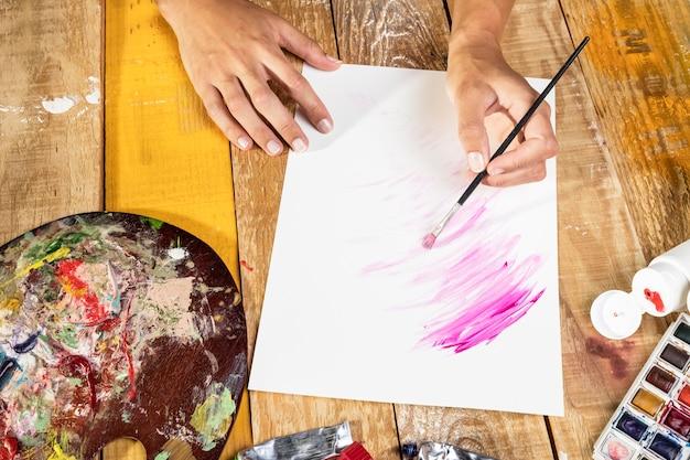Художник с помощью кисти с краской на бумаге