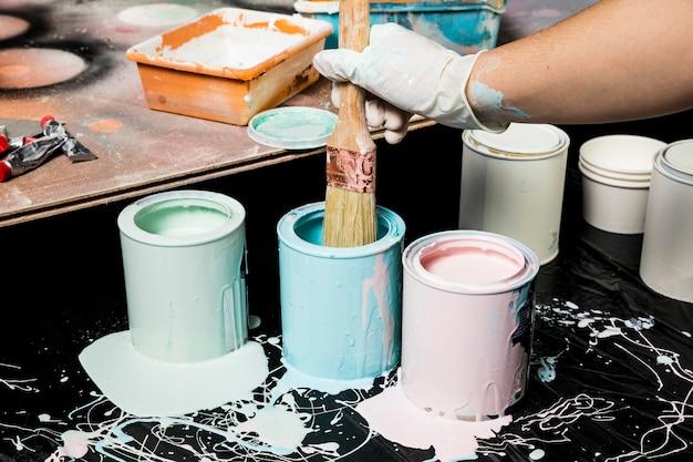 Художник с помощью краски из банок