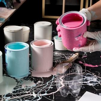 Художник, используя розовую краску из банки