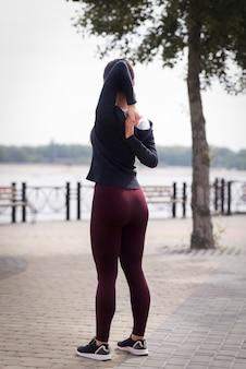 屋外ストレッチ運動の若い女性