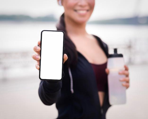 Крупным планом спортивная женщина, держащая мобильный телефон