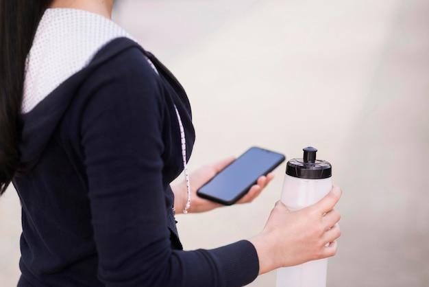 Женщина конца-вверх держа мобильный телефон и бутылку с водой
