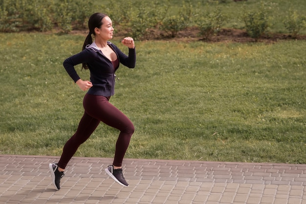 屋外を実行している側面図の若い女性