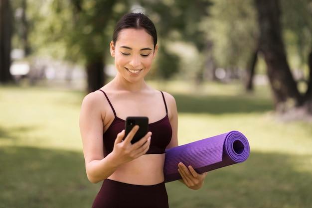 Портрет молодой женщины, проверка мобильного телефона