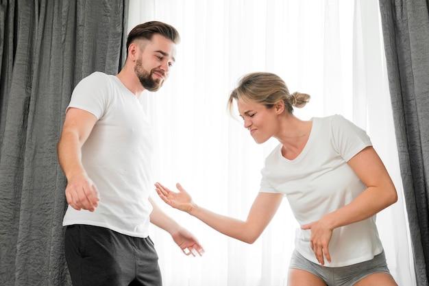 幸せなカップルが屋内でプレイモードで空手をやって