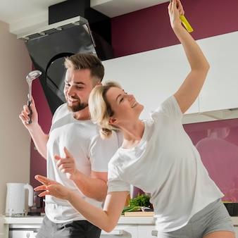 屋内で幸せであり、キッチンで踊るカップル