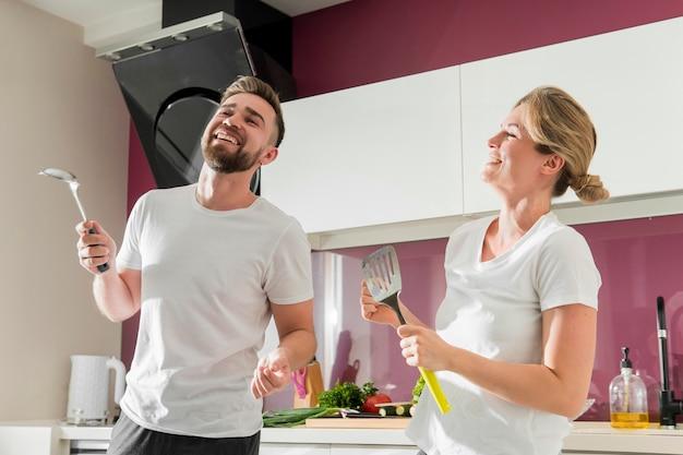 屋内でキッチンで踊るカップル