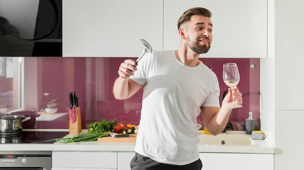 Мужчина пьет вино и дурачится на кухне