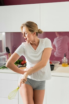 Женщина танцует на кухне