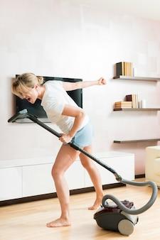 掃除機をマイクとして使用している女性