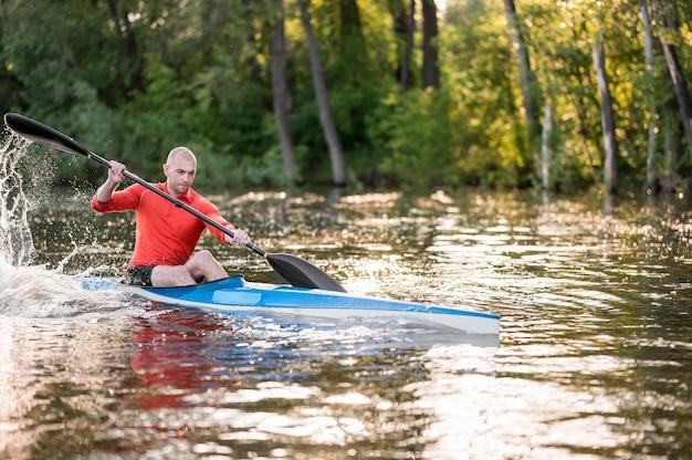 青いカヌーで漕ぐ男