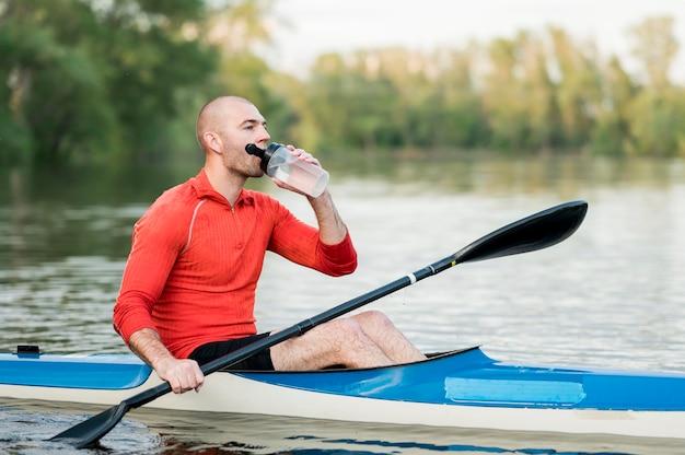 Мужчина пьет воду в каяке