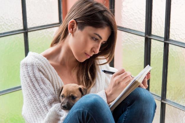 Женщина сбоку с собакой и тетрадью