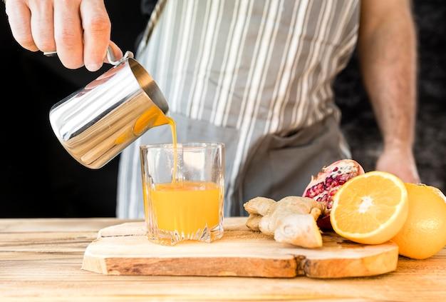オレンジジュースの正面図を作る男