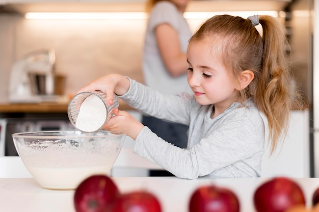 Вид спереди маленькой девочки, приготовление пищи дома