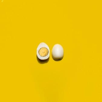 トップビューの黄色の背景にゆで卵