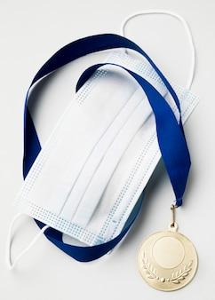 Спортивная медаль рядом с медицинской маской