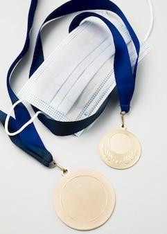 Вид сверху спортивная медаль рядом с медицинской маской