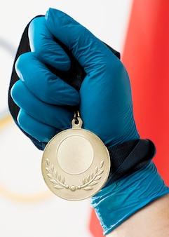 メダルのクローズアップを持っている人