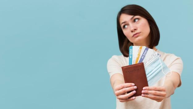 Женщина вид спереди держит некоторые билеты на самолет с копией пространства