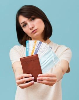 Женщина вид спереди держит билеты на самолет