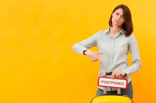 コピースペースで延期されたサインを押しながら彼女の荷物の隣に立っている若い女性